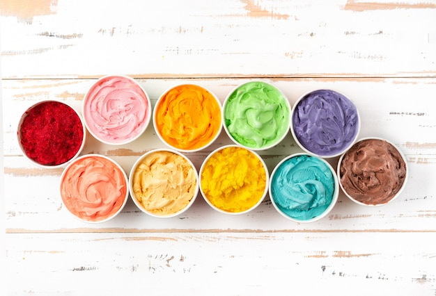 Many cups with colorful rainbow ice cream. top view