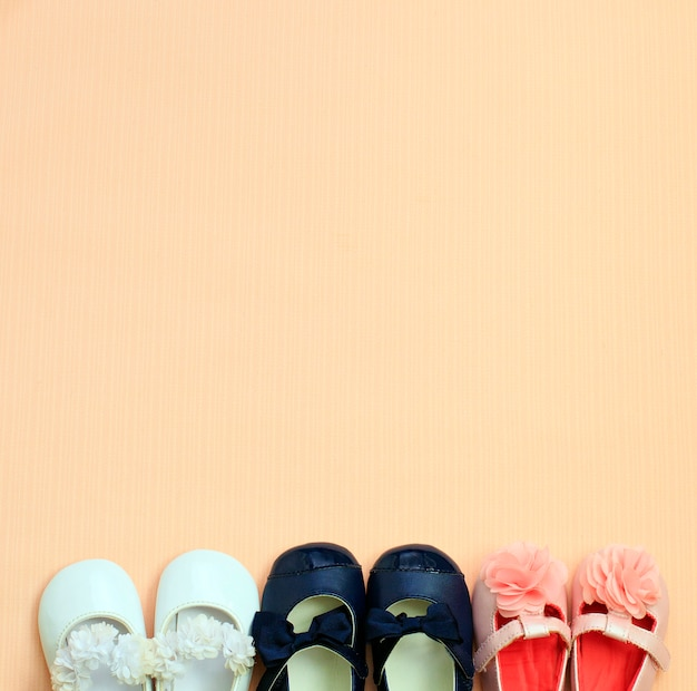 Many cute baby shoe placed on pink background , top view