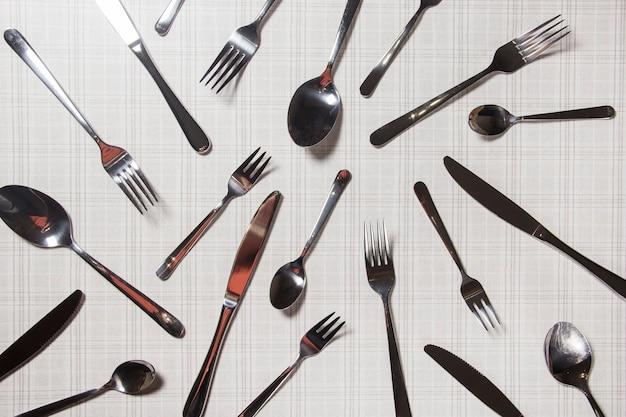 많은 칼붙이 포크, 칼, 숟가락 위쪽 전망은 밝은 배경에 놓여 있습니다. 미니멀한 컨셉.
