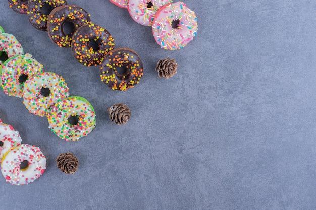 Molte delle deliziose ciambelle con pigne nelle quali su una superficie grigia