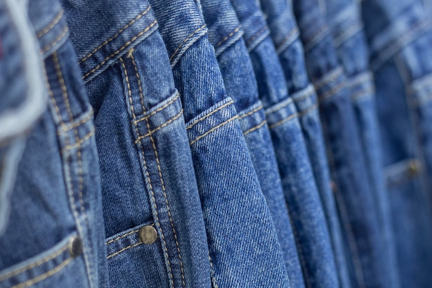 Many denim jeans hanging on a rack