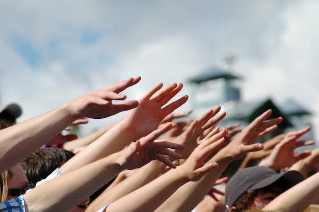 多くの絶望的な手が横向きに空中に手を伸ばしてコンサート/ラリーに出る