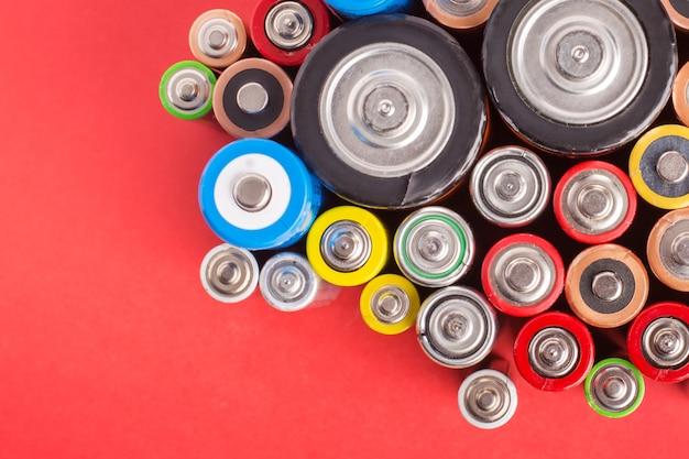 Много разных щелочных батарей на красном фоне