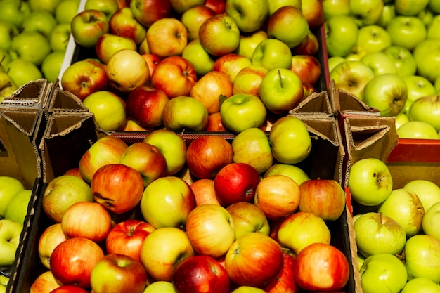 Many different apples in boxes on the market counter. health and vitamins from nature.