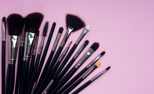 Множество разных кистей для профессионального косметического макияжа на розовом фоне. макет.
