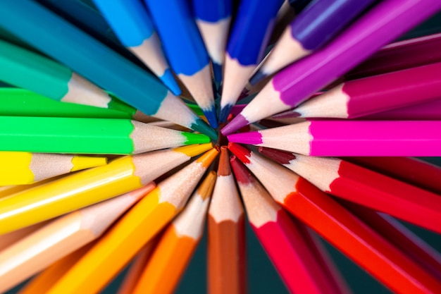 Many different colored pencils reflected on black
