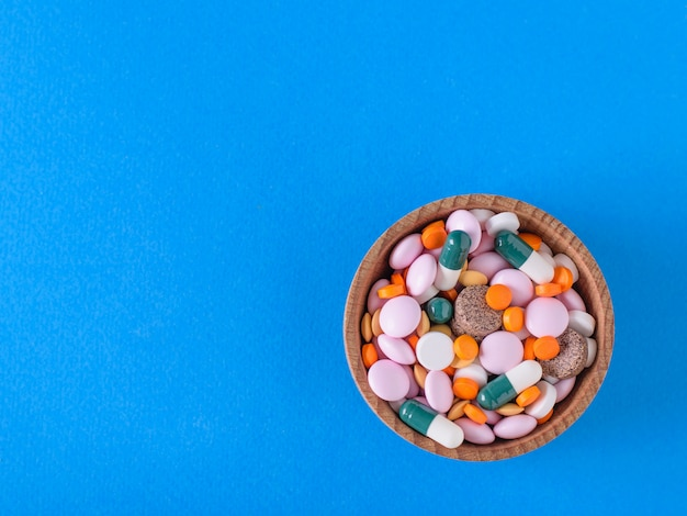 Many different colored tablets in a wooden bowl