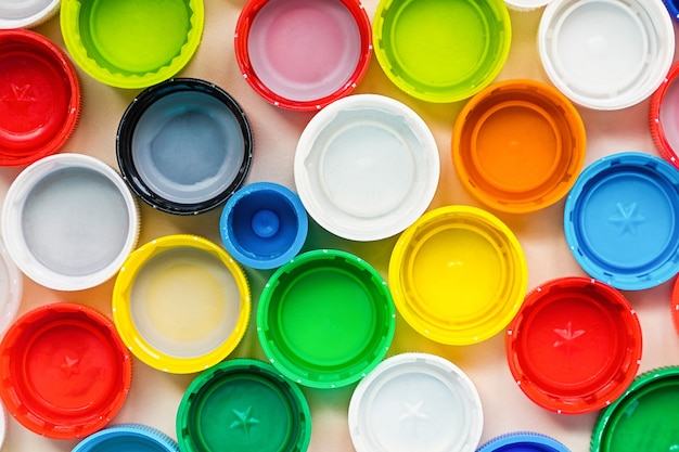 Много различных красочных пластиковых крышек фона. концепция утилизации.