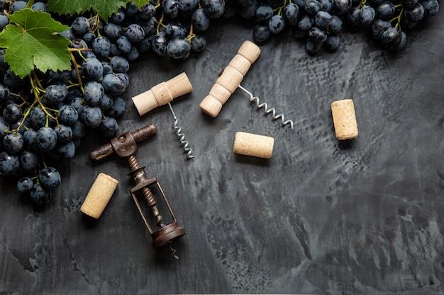 Many different corkscrews varieties with open wine corks on dark concrete background, black grapes. degustation winetasting of wines drink. corkscrews types in wine bar restaurant.