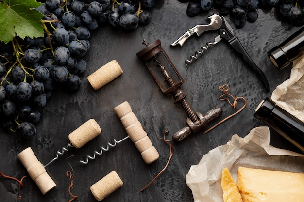 Many different corkscrews with open wine corks on dark concrete background in frame made of black grapes. degustation winetasting of wines drink. wine bar restaurant. flat lay.