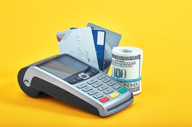 노란색 배경에 다양한 신용 카드, 달러 지폐 및 결제 단말기, 클로즈업