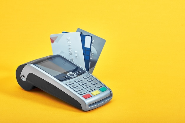Many different credit cards and payment terminal on yellow background, closeup.