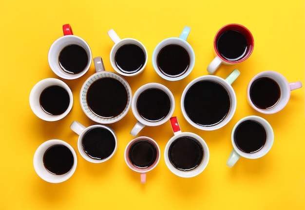 Many different cups of coffee on yellow background. top view,flat lay,copy space.