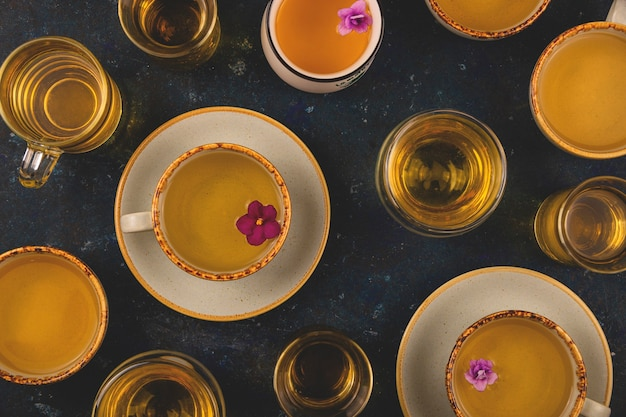 Many different cups of tea with violet flowers on dark blue background. top view layout