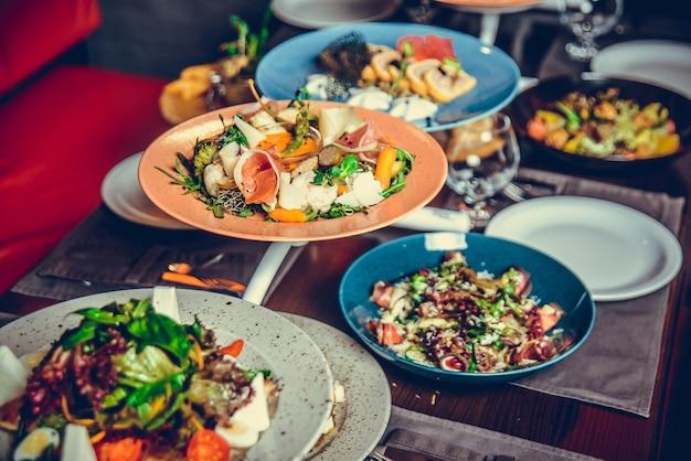 Много разных блюд в ресторане, белая тарелка на столе с гарниром, крекер