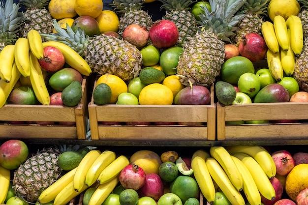 Много разных свежих фруктов в корзинах в продуктовом магазине
