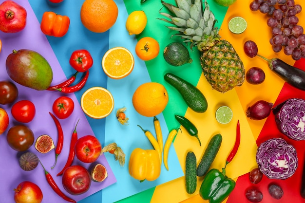 Many different fruits and vegetables on rainbow background