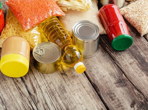 다양한 식료품 제품. 주식 제품 원시 곡물 곡물 식료품 파스타와 나무 테이블에 통조림 식품의 집합입니다. 음식 배달 개념을 기부하십시오.