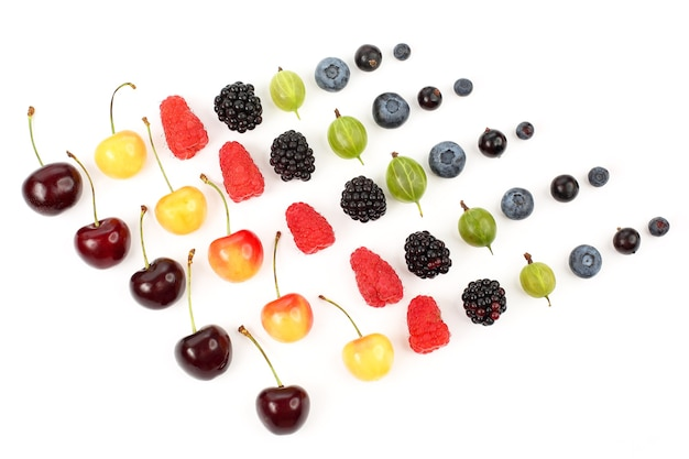 Many different juicy berries are arranged in order on a white background. healthy fresh vegetables and food