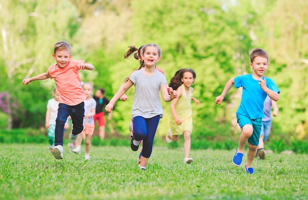 日当たりの良い夏の日にカジュアルな服で公園で走っている多くの異なる子供、男の子と女の子