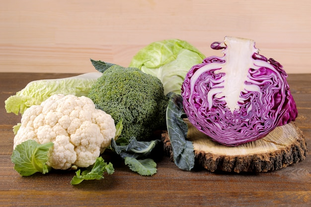 Many different kinds of cabbage on a brown wooden surface
