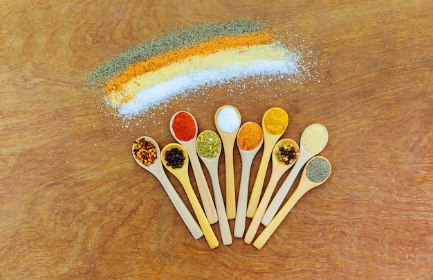 Many different kinds of spices from asia. beautiful wooden spoons with spices top view.