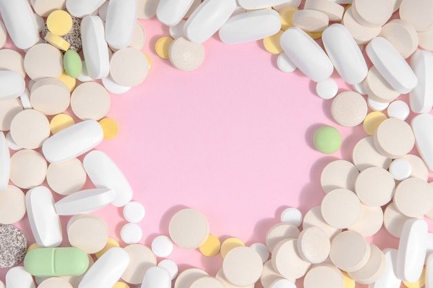 テキストのための場所とピンクの背景に多くの異なる薬