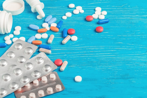 Много разных таблеток на синем фоне деревянных