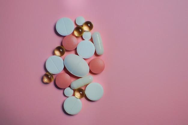 白いテーブルの上の多くの異なる錠剤covid19に対する多くのカラフルな異なる錠剤