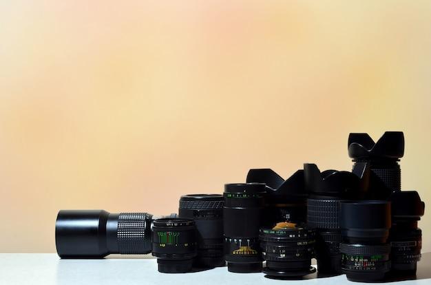 Много разных профессиональных объективов для зеркальных камер лежит на бесцветном столе
