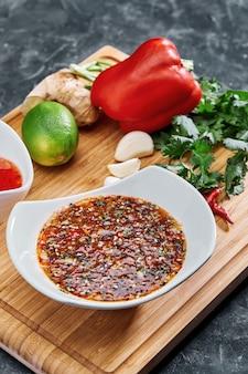 Множество различных специй, овощей и ингредиентов, а также зелень для приготовления домашнего соуса.