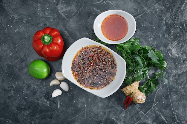 Many different spices, vegetables and ingredients, and fresh herbs for making homemade sauce.