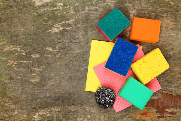 Many different sponges for cleaning on the old wooden background.