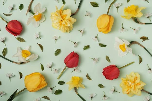 Много разных весенних цветов на зеленом фоне. тюльпаны, нарциссы и другие крупные и мелкие цветы. концепция праздников и поздравлений.