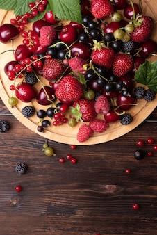 Много разных летних ягод на темном деревянном фоне, клубника, малина, вишня, смородина, крыжовник на подносе, здоровое питание, крупный план.