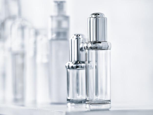 Множество разных прозрачных флаконов с дозирующим насосом для духов или других жидкостей.