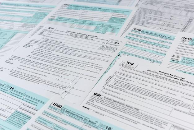 多くの異なる米国の税務フォーム。 4月に記入するためのw4w9および1040フォーム。課税時間