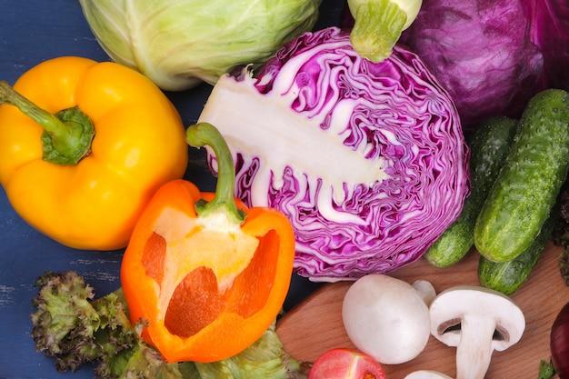 青い木製の表面に多くの異なる野菜