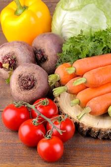 Много разных овощей на деревянной подставке на коричневой деревянной поверхности