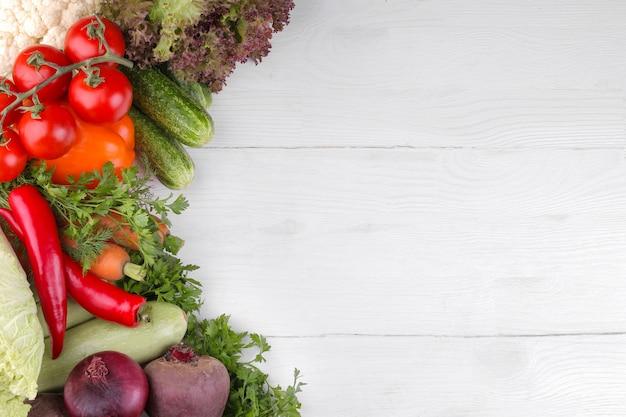 白い木の表面に多くの異なる野菜