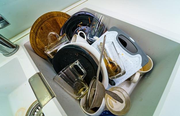 В раковине на кухне много грязной посуды. стаканы и тарелки с остатками еды.