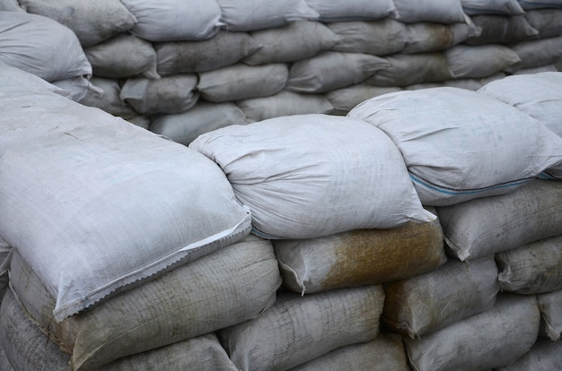 Many dirty sand bags for flood defense. protective sandbag barricade for military use. handsome tactical bunker