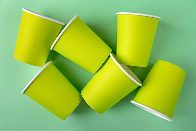 뚜껑이없는 테이크 아웃 커피 또는 차를위한 많은 일회용 빈 모의 종이 녹색 컵이 배경에 놓여 있습니다.