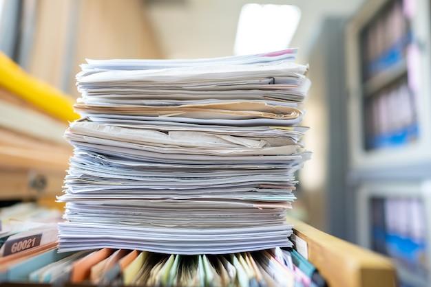 多くの書類がオフィスに積み上げられています。