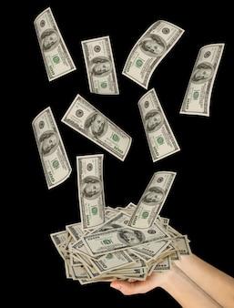 Многие доллары падают на руку женщины с деньгами