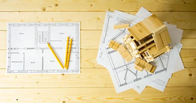 Многие рисунки для строительства, карандаши и домик на деревянном фоне.