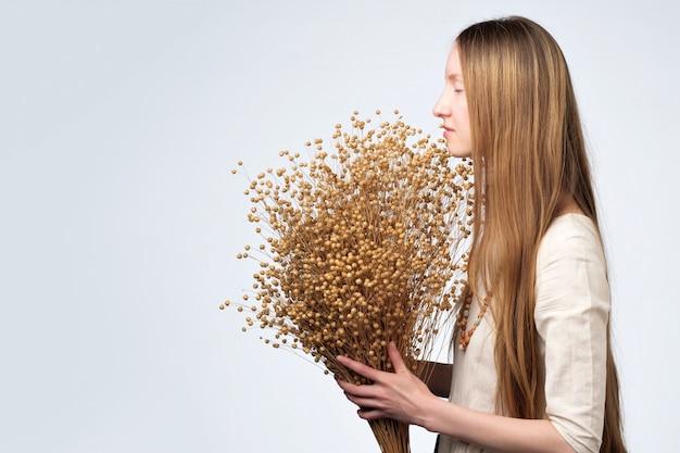 Множество засушенных цветов льна в руках красивой девушки с длинными волосами.