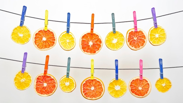Many dried pieces of different citrus fruits hang on colored clothespins. healthy and vitamin food