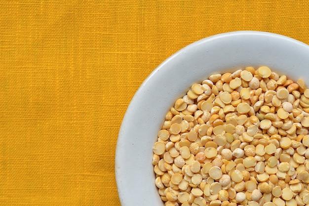 Многие сушеные гороховые бобы в белой миске на желтой скатерти