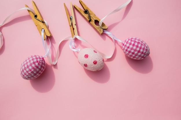 トレンディなピンクのパステル調の背景に多くのイースターエッグ。卵は手描きです。
